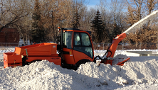 Holder removing deep compacted snow with center driven snow blower.