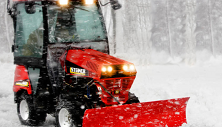 Steiner compact tractor clearing snow with power angle blade