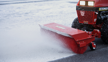 Steiner compact tractor clearing snow with Rotary Sweeper