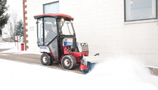 Ventrac 4500 clears sidewalk with snow broom. Click image to see broom specs.
