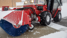 Ventrac snow broom-sweeper clearing snow to dry pavement