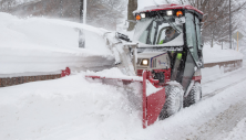 Ventrac 2-stage blower clearing deep snow off sidewalk